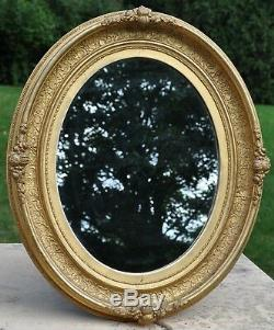 French Antique Louis XVI oval gilt frame mirror, gold leaf on carved wood